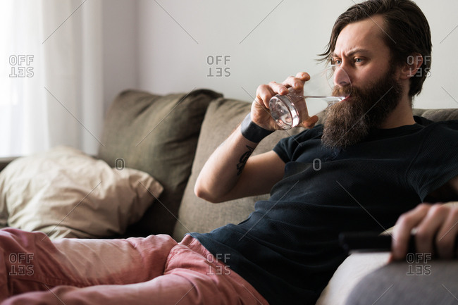Man drinking a water sitting on a couch and surfing the channel. Horizontal indoors shot.