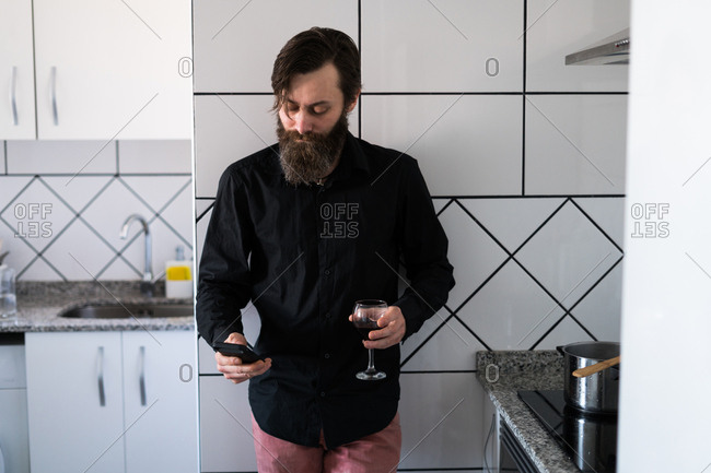Handsome bearded man standing in the kitchen with wine browsing phone.