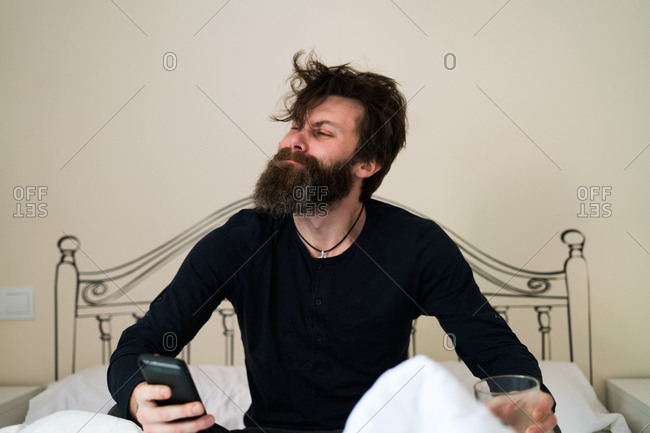 Sleepy bearded man with the phone in the morning. Horizontal indoors shot.