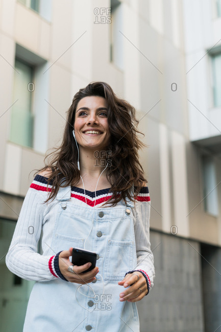 Young brunette in trendy clothing listening to music with headphones and smart phone at street.