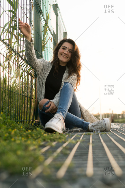 Young smiling woman wearing trendy outfit and posing on ground near fence while smiling at camera.