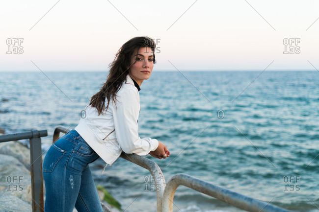 Beautiful brunette in casual outfit posing near metal fence with sea on background.