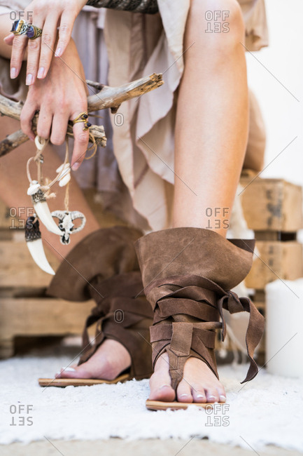 Young woman with the stick wearing boho sandals. Vertical indoors shot.