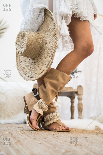 The female legs in boho sandals and a hat. Vertical indoors shot.