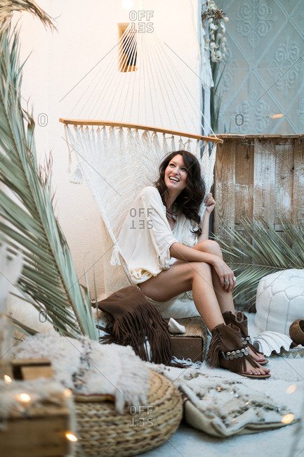 Pretty young girl sitting in hammock and looking away. Vertical indoors shot.