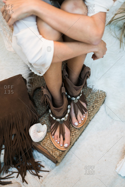 Legs of woman embraced her knees wearing boho shoes.