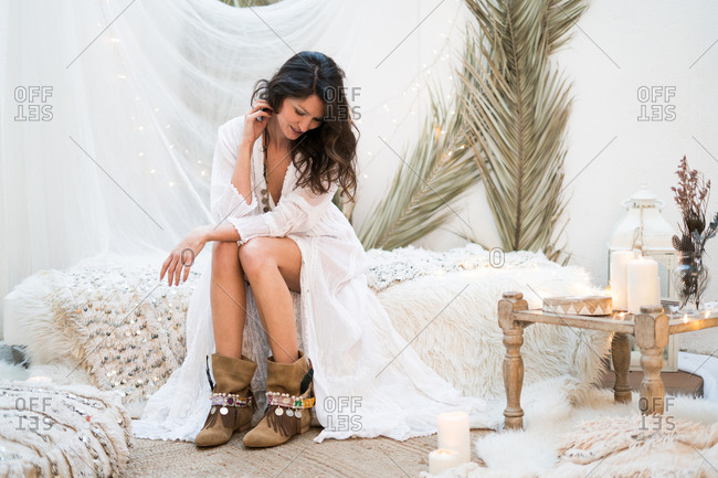 Young woman sitting in the bedroom decorated in boho style. Horizontal indoors shot.