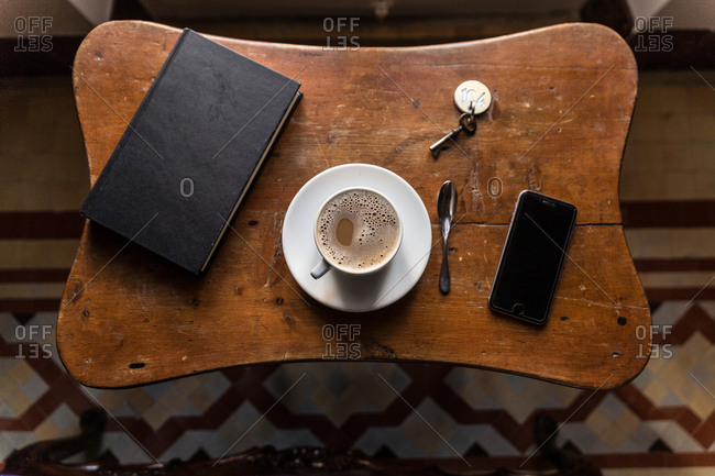 From above shot of coffee, smartphone and book on wooden table.