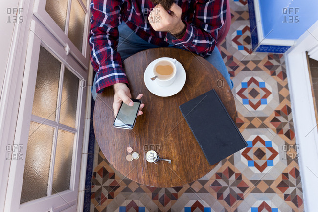From above shot of man in hat and checkered shirt sitting at table with phone and coffee.