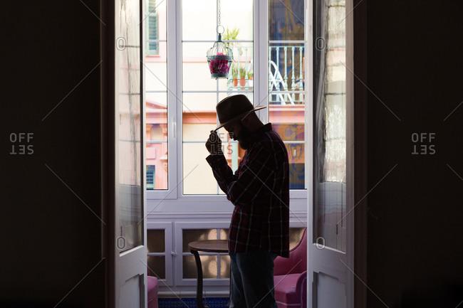 Silhouette of male in hat standing in doorway of balcony.