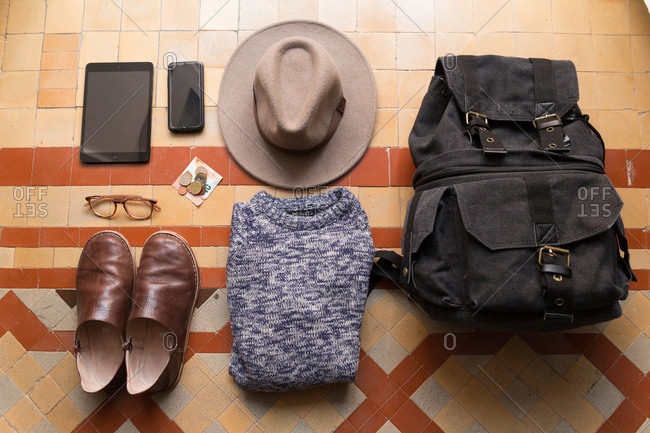 Shot of daily set of person with backpack, clothing, gadgets and money.