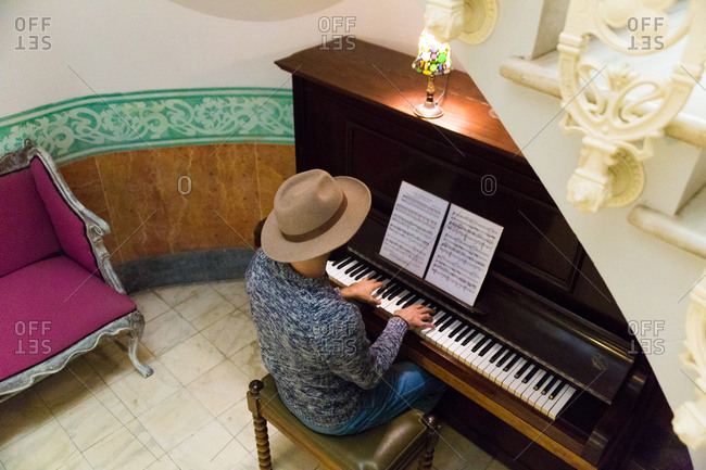 From above shot of man in hat playing piano in elegantly decorated room.
