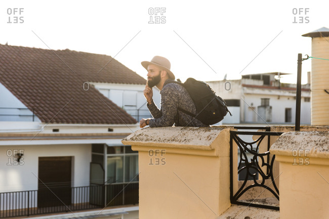 Stylish male with backpack on balcony