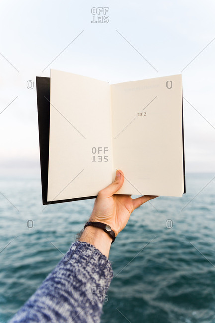 Crop shot of male hand in sweater holding notebook on background of sea.