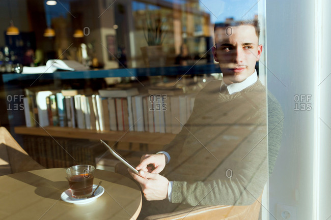 Young businessman sitting in the cafe and browsing the tablet. Horizontal indoors shot.