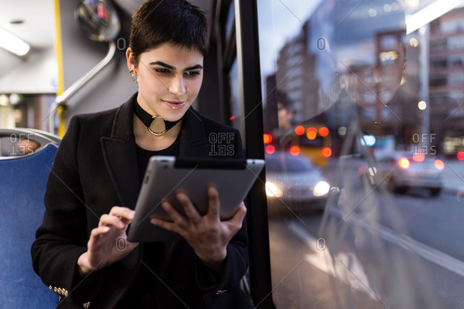 Horizontal shot of young woman riding a public transport and browsing the tablet.