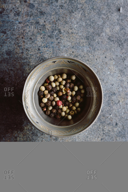 Peppercorns, in metal bowl on blue grunge background