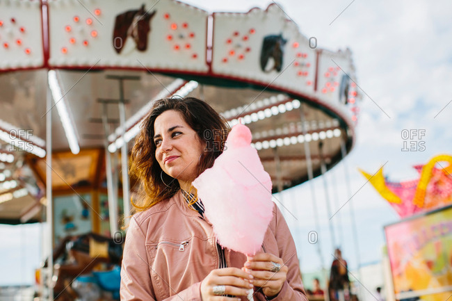 Smiling female holding a cotton candy near the merry-go-round. Horizontal outdoors shot.