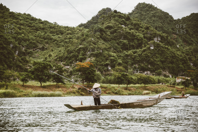 Woman in conical hat on canoe and rowing. Traditional asian boat made of wood.