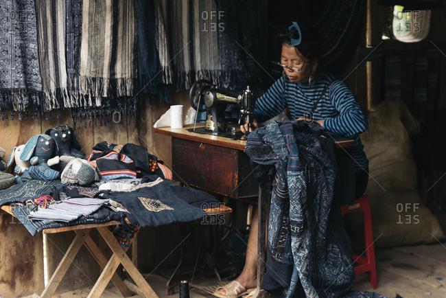 SAPA, VIETNAM - AUGUST 14: Vietnamese elder woman working making souvenirs on August 14, 2016 in Sapa, Vietnam.