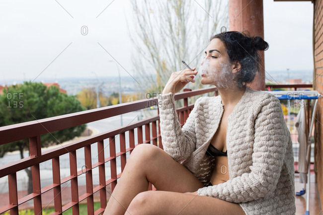 Brunette female in lingerie and cardigan smoking sitting on balcony
