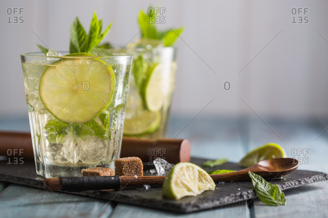 Mojito in glass on wooden blue table with lime and mint