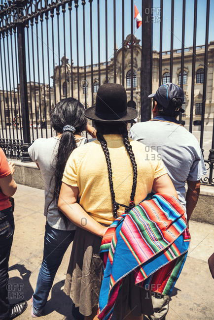 LIMA, PERU - DECEMBER 26, 2016: Back view of native people looking at the Government Palace in Lima, Peru. Vertical outdoors shot.