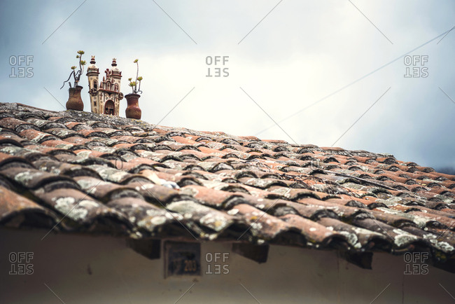 The tower of small temple over tiled roof of a house in small village in Ayacucho, Peru.
