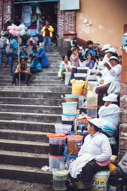 AYACUCHO, PERU - DECEMBER 30, 2016: The people sitting on stairs and selling goods in a street of Ayacucho, Peru.