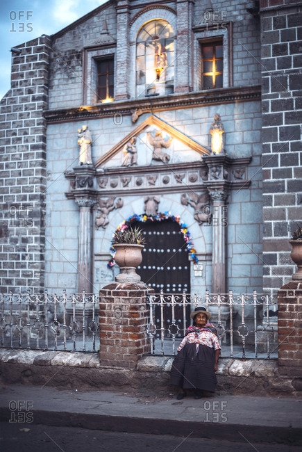 AYACUCHO, PERU - DECEMBER 30, 2016: Vertical outdoors shot of old woman sitting at the church in a street of Ayacucho, Peru.