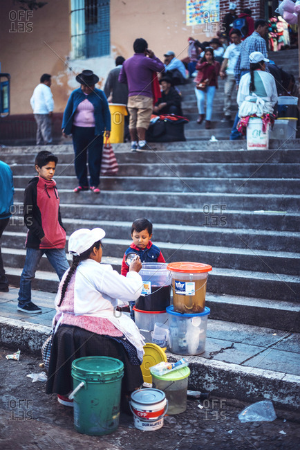 AYACUCHO, PERU - DECEMBER 30, 2016: A woman in street market selling goods to child customer in a street of Ayacucho, Peru.