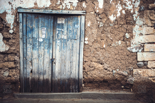 Horizontal outdoors shot of an old rough door in a small village in Ayacucho, Peru.