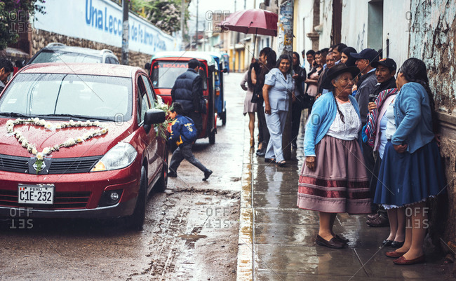 AYACUCHO, PERU - DECEMBER 30, 2016: A group of wedding guests standing on the pavement in Ayacucho, Peru.