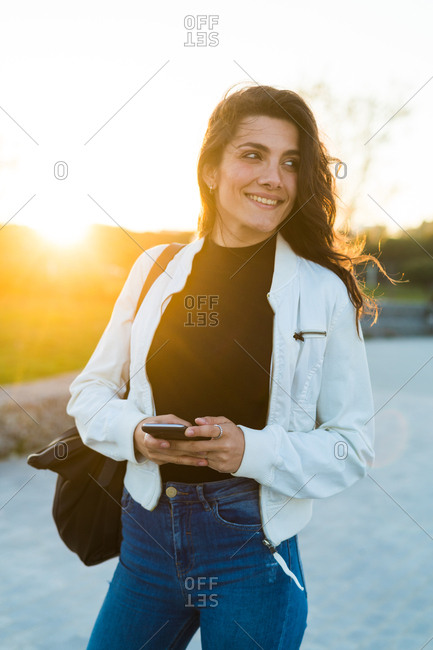 Beautiful laughing brunette in trendy clothing using phone while looking away in back lit.