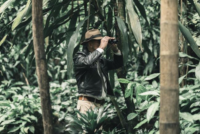 Senior explorer inspecting bush with binoculars.