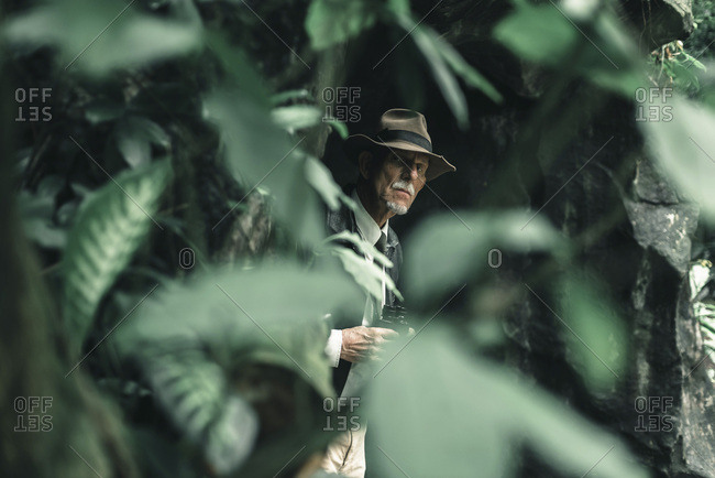 Senior explorer with hat looking alert into forest.