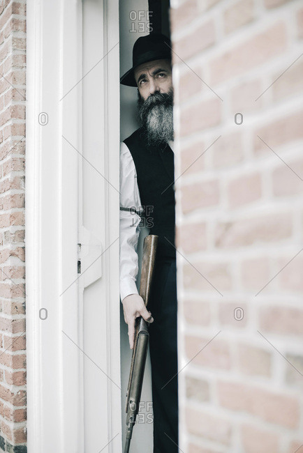 Mysterious man with hat and long beard standing with rifle in open door.