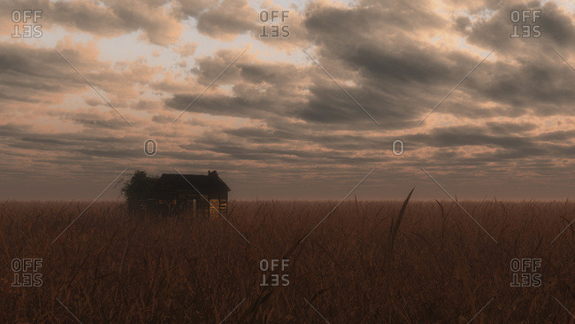 Old dilapidated wooden barn in field under cloudy sky.