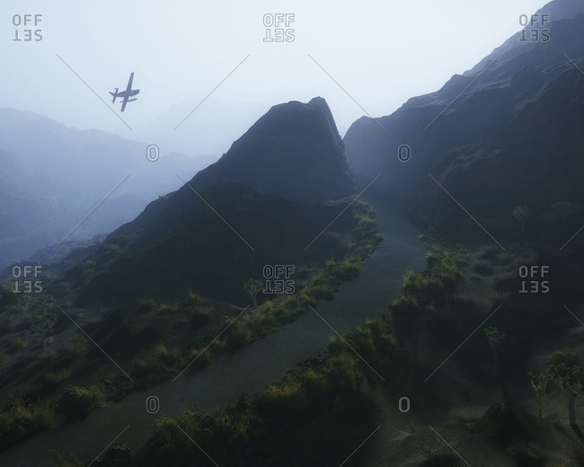 Single engine airplane over misty mountain landscape with winding road.