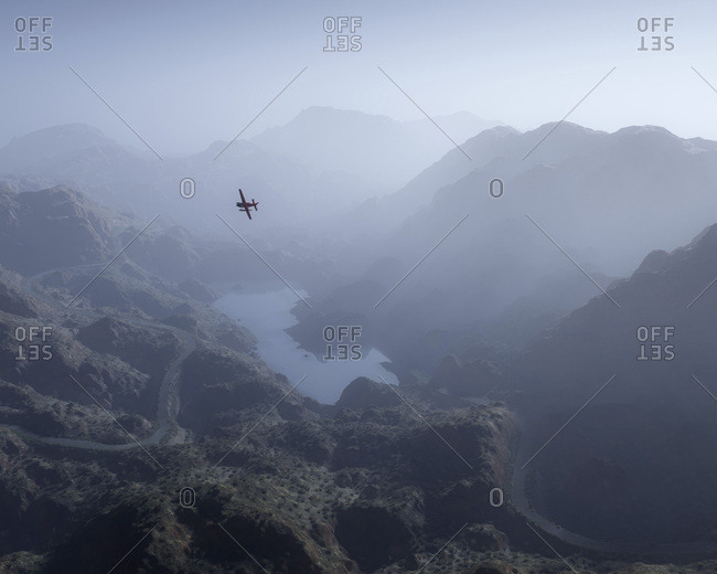 Aerial of private airplane over misty mountain landscape with lake and winding road.