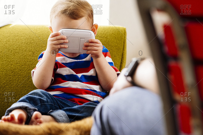 Baby boy playing handheld video game while sitting in armchair at home