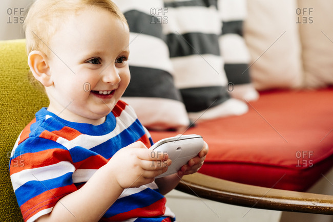 Happy baby boy looking away while holding handheld video game at home