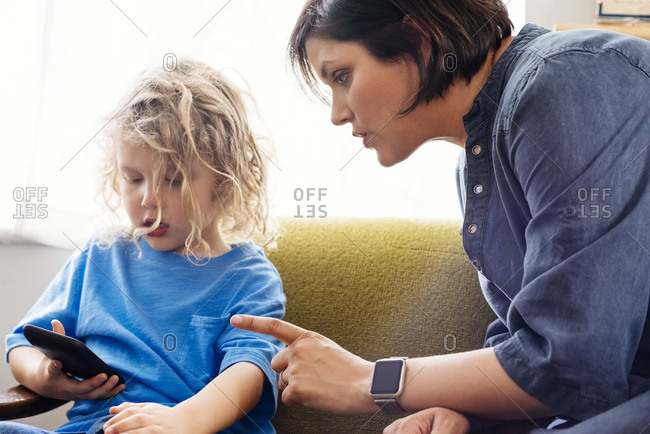 Side view of angry mother scolding boy using smartphone