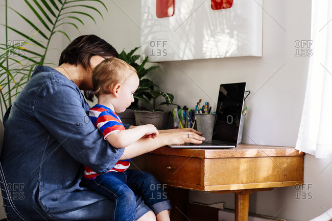 Side view of mother using laptop with baby boy on lap in home office