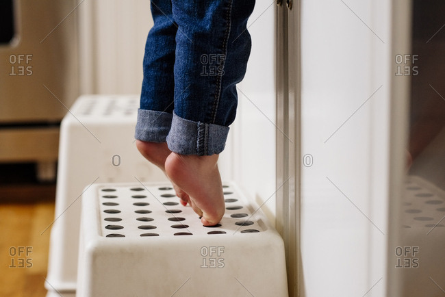 Low section of baby boy tiptoeing on step stool in kitchen at home