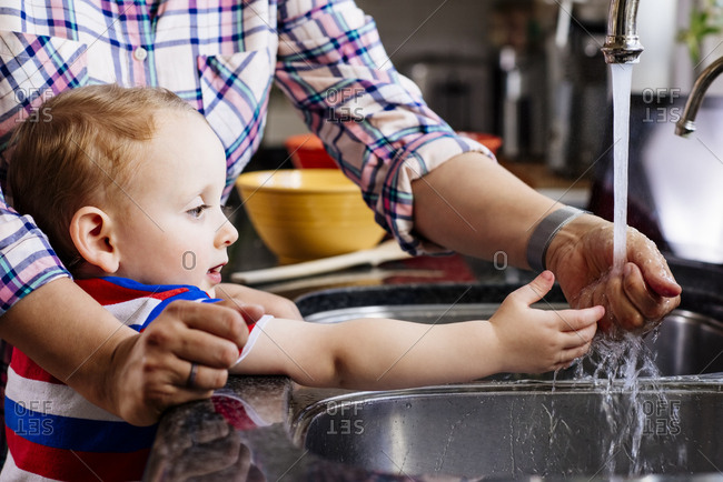 Midsection of mother assisting baby boy in washing hand at kitchen counter