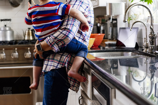 Midsection of mother carrying son while standing at kitchen counter