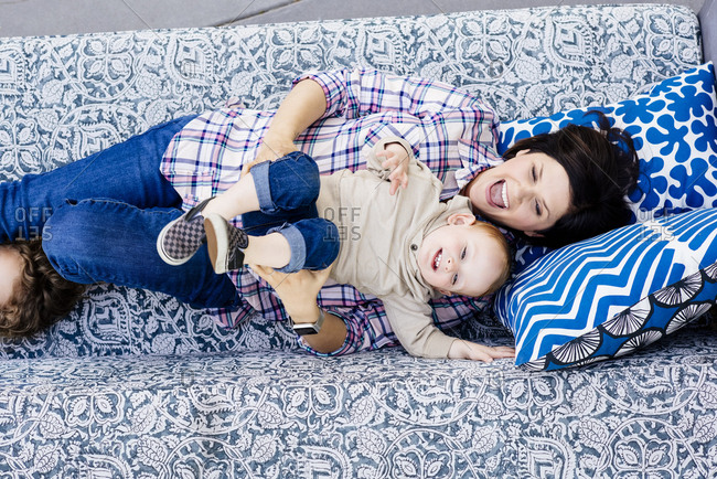 Directly above shot of cheerful woman screaming while lying with baby boy on sofa at home