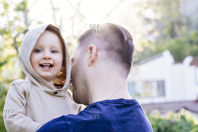 Portrait of cheerful baby boy being carried by father in yard during sunny day