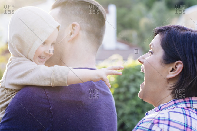 Father carrying baby boy in yard while mother makes funny face